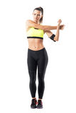 Pretty woman runner flexing shoulder exercise while stretching arm. Stock Photography