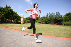 Pretty woman running outdoors. Training at park Royalty Free Stock Photography