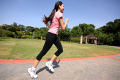 Pretty woman running outdoors. Training at park Royalty Free Stock Image