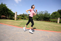 Pretty woman running outdoors training at park. With earphone Royalty Free Stock Photo