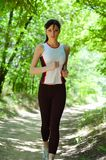 Pretty woman running in the park Royalty Free Stock Image