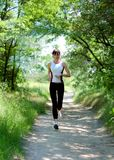 Pretty woman running in the park. Pretty young woman running in the park Royalty Free Stock Images