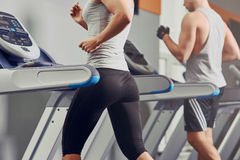 Pretty woman running on treadmill with fit young man on background Stock Images