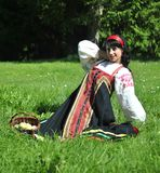 Pretty woman in russian traditional costume. Sitting on the grass stock photo