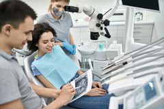 Pretty woman`s teeth treatment in dental clinic stock image