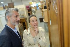 Pretty woman with salesman in furniture store. Pretty women with salesman in furniture store woman stock photos