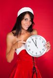 Pretty Woman In Santa Claus Costume Showing Clock Stock Image