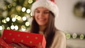 Pretty Woman in Santa Hat Astonished with the Surprise Inside of the Red Box. Cute Smiling Girl opening Christmas Gift stock footage