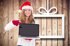 Pretty woman in santa hat and gloves pointing at laptop Stock Photos