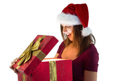 Pretty woman in santa hat opening a gift smiling at it Royalty Free Stock Images