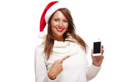 Pretty woman in a Santa hat reading an sms Royalty Free Stock Photos