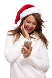 Pretty woman in a Santa hat reading an sms Stock Photo