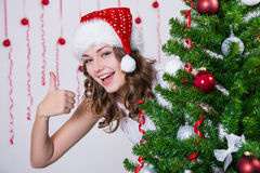 Pretty woman in santa hat thumbs up near Christmas tree Royalty Free Stock Photo