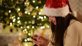 Pretty Woman in Santa Hat Using Black Smartphone and Smiling on Background Christmas Tree. Beautiful Girl in Xmas Cap