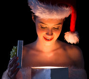 Pretty woman in santa outfit opening a gift smiling at it Stock Photo