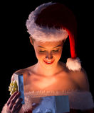 Pretty woman in santa outfit opening a gift smiling at it Stock Image