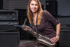 Pretty woman with saxophone Royalty Free Stock Photography