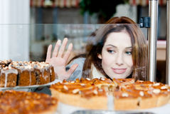 Pretty woman in scarf looking at the bakery showcase. Lady in scarf looking at the bakery window full of different pieces of cakes Royalty Free Stock Photos