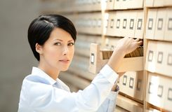 Pretty woman searches something in card catalog Royalty Free Stock Photos