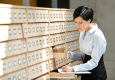 Pretty woman searches something in card catalog. Composed of set of wood boxes at the library. Study Royalty Free Stock Image