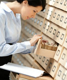 Pretty woman searches something in card catalog Royalty Free Stock Images