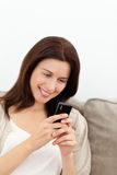 Pretty woman sending a sms with her mobile phone. On the sofa Stock Images