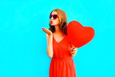 Pretty woman sends an air kiss with a balloons on blue. Background Royalty Free Stock Photo
