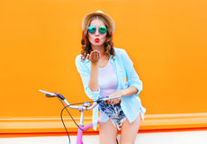 Pretty woman sends air kiss on bicycle over colorful orange Stock Photo