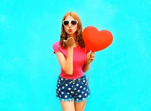Pretty woman sends an air kiss holds a red balloon in the shape. Of heart on blue background Royalty Free Stock Photography