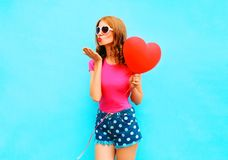 Pretty woman sends an air kiss holds red balloon in the shape. Of heart on a blue background Royalty Free Stock Photos