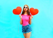 Pretty woman sends an air kiss holds a red balloons in the shape. Of heart on blue background Stock Images