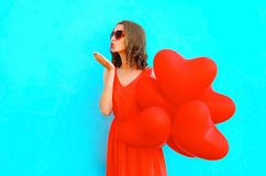 Pretty woman sends an air kiss with red air balloons on blue bac. Kground Stock Photo