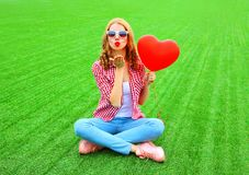 Pretty woman sends an air kiss with red balloon in the shape of a heart. On the grass Royalty Free Stock Images