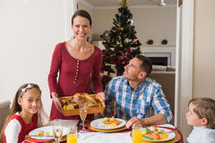 Pretty woman serving roast turkey to her family Stock Image