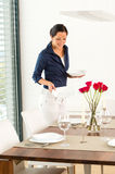 Pretty woman setting table dining room preparing royalty free stock photography
