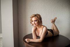 Pretty woman in sexy black lingerie lying on table and looking at camera Royalty Free Stock Images
