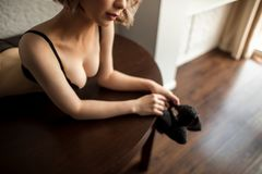 Pretty woman in sexy black lingerie lying on table and looking at camera Stock Images