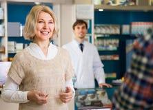 Pretty woman shopper buys drugs. Pretty women shopper buys drugs at the pharmacy Royalty Free Stock Photos