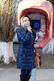 Pretty woman shopper at a public phone booth Stock Image