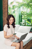 Pretty woman shopping online with credit card at home. Stock Photography