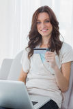 Pretty woman shopping online and smiling at camera Stock Images