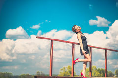 Pretty woman in short black dress on the bridge. Young brunette girl in short black dress in red high heels on the bridge Stock Photo