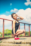 Pretty woman in short black dress on the bridge. Young brunette girl in short black dress in red high heels on the bridge Stock Images