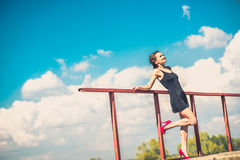 Pretty woman in short black dress on the bridge. Young brunette girl in short black dress in red high heels on the bridge Royalty Free Stock Photography