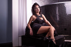 Pretty woman in a short black dress sitting on a soft chair. WOman with curly hair and red lips. Pretty woman in a short black dress sitting on a soft chair Stock Photos