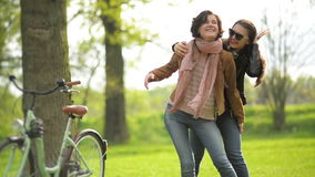 Pretty Woman with Short Curly Hair Wearing Jacker and Jeans is Carrying Her Female Friend in Sunglasses on the Shoulders. Smiling Happy Girls Spending Time stock footage