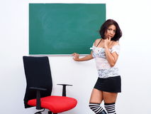 Pretty woman in short dress stands in front of green chalkboard Stock Image