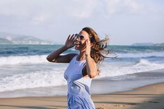 Pretty woman in short sarafan and sun glasses with fluttering hair stands on the beach near the ocean and waves, stock photos