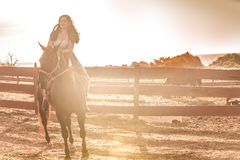 Pretty Woman shot into sun on her horse Stock Images