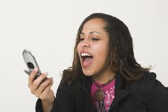 Pretty woman shouting into a c. Pretty Afro-American woman shouting into a cell phone. Photographed against a white background Stock Images